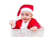 逗人喜爱的男孩在坐在箱子的圣诞老人盖帽 免版税库存图片