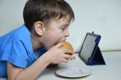 逗人喜爱的男孩在家长沙发的,吃汉堡包和看片剂,观看的动画片或者谈与朋友 免版税图库摄影