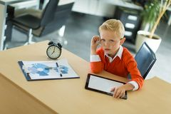 逗人喜爱的男孩坐在书桌在办公室,并且用途压片个人计算机 免版税库存照片