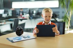 逗人喜爱的男孩坐在书桌在办公室,并且用途压片个人计算机 免版税库存图片