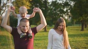 逗人喜爱的男孩坐父亲肩膀在家庭期间在公园首先走 股票录像