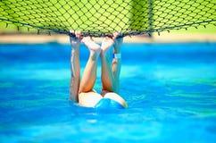 逗人喜爱的男孩孩子获得乐趣,做特技在排球网在水池 免版税库存图片