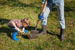 逗人喜爱的男孩帮助的爷爷在后院 库存图片