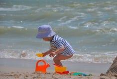 逗人喜爱的男孩播放在海滩的一个桶 免版税库存图片
