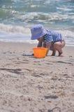 逗人喜爱的男孩播放在海滩的一个桶 免版税图库摄影