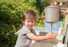 逗人喜爱的男孩洗他的手在盥洗盆下 库存图片