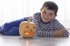 逗人喜爱的男孩用在万圣夜服装的南瓜在地板上 免版税库存照片