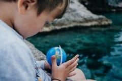 逗人喜爱的男孩看地球在海附近 库存照片