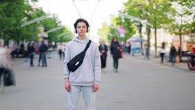 逗人喜爱的男孩缩小定期流逝站立在街道的耳机的在城市 影视素材