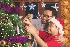 逗人喜爱的男孩装饰与父亲的一棵杉树 库存图片