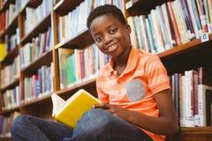 逗人喜爱的男孩阅读书在图书馆里 库存照片