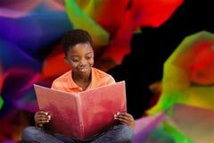 逗人喜爱的男孩阅读书的综合图象在图书馆里 图库摄影