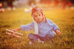 逗人喜爱的男孩,使用与在日落的飞机在公园 免版税库存图片