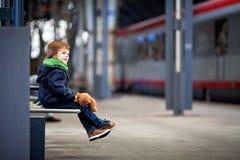 逗人喜爱的男孩,坐与玩具熊的一条长凳,看火车 免版税图库摄影