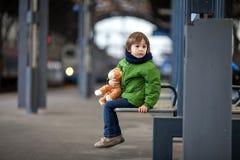 逗人喜爱的男孩,坐与玩具熊的一条长凳,看火车 图库摄影