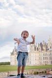 逗人喜爱的男孩,有在Chambord大别墅前面的乐趣夏令时 图库摄影