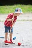 逗人喜爱的男孩,演奏槌球 免版税库存图片