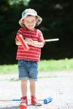 逗人喜爱的男孩,演奏槌球 免版税库存照片