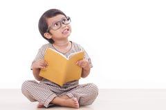 逗人喜爱的男孩读一本书 库存照片