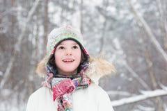 逗人喜爱的男孩画象在雪风暴下的森林 库存照片