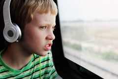 逗人喜爱的男孩画象有耳机的 库存照片
