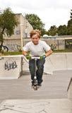 逗人喜爱的男孩scooting与他的滑行车 免版税库存图片