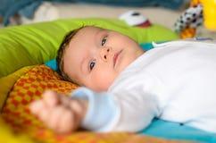 逗人喜爱的男婴在五颜六色的地毯说谎 图库摄影