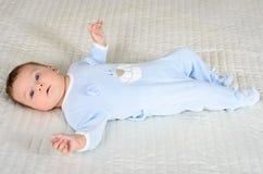 逗人喜爱的男婴在灰色地毯说谎 库存图片
