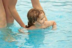 逗人喜爱的男婴学会游泳在母亲帮助下 免版税库存图片