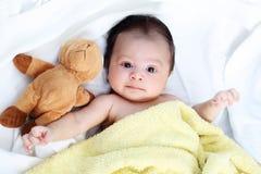 逗人喜爱的男婴对在白色床上的黄色毯子和玩偶熊可爱的朋友满意 免版税库存图片