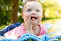 逗人喜爱的男婴画象有说谎在毯子的唐氏综合症的在自然的夏日 图库摄影