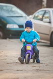 逗人喜爱的男婴骑他的第一辆连续自行车 免版税图库摄影