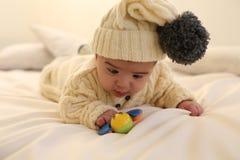 逗人喜爱的男婴,穿被编织的衣裳,使用与玩具在舒适家 免版税库存照片