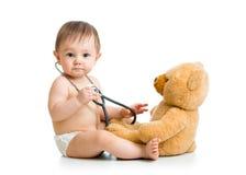 逗人喜爱的男婴weared有听诊器和玩具的尿布 免版税库存图片