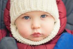 逗人喜爱的白种人男婴在一条白色被编织的温暖的帽子和围巾的2岁严重注视着蓝色e照相机传神神色  免版税库存照片