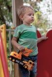逗人喜爱的白种人白肤金发的男婴站立与在儿童操场的一种玩具黄色挖掘机 单独,严肃和humile expressi 免版税图库摄影