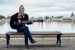 逗人喜爱的白肤金发的使用的吉他,当坐长凳时 免版税库存照片