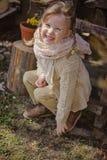 逗人喜爱的白肤金发的儿童女孩获得乐趣在早期的春天庭院 免版税库存照片
