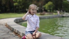 逗人喜爱的白肤金发的女孩坐湖的岸和从她的面孔取消头发 乘坐在滑行车 股票录像