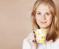年轻逗人喜爱的白肤金发的女孩饮用的咖啡接近在温暖的褐色bac 免版税库存图片
