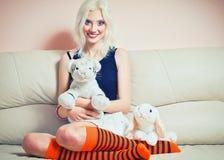 逗人喜爱的白肤金发的女孩画象用兔子和老虎 图库摄影