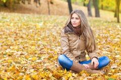 逗人喜爱的白肤金发的妇女在秋天 库存照片
