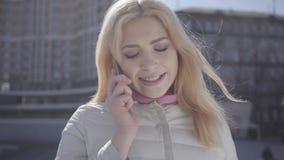 逗人喜爱的白肤金发的妇女画象有牙括号的在城市街道的温暖的外套身分谈话由手机 都市 股票录像