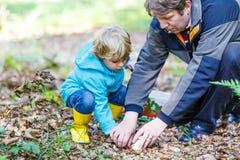 逗人喜爱的白肤金发的孩子搜寻蘑菇的男孩和他的父亲 免版税库存照片