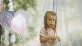逗人喜爱的白肤金发的小孩女孩画象在公园 免版税库存照片