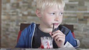 逗人喜爱的白肤金发的男孩饮用的草莓奶昔 股票视频