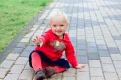 逗人喜爱的白肤金发的婴孩坐地面 库存图片