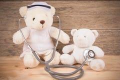 逗人喜爱的白色玩具熊穿戴护士用途stehoscope检查健康bea 库存图片