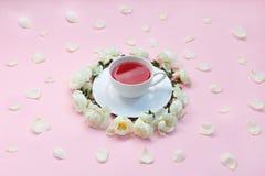 逗人喜爱的白色玫瑰和他们的瓣围拢的一杯茶的上部视域在粉红彩笔背景 关闭茶 ?? 免版税库存照片