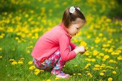 逗人喜爱的相当小女孩用黄色蒲公英 免版税图库摄影